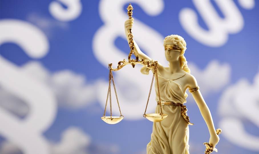 Justizia vor blauem Himmel mit Paragraphen